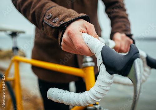 Tablou Canvas a young man with hands on the steering wheel of bicycle near the lake