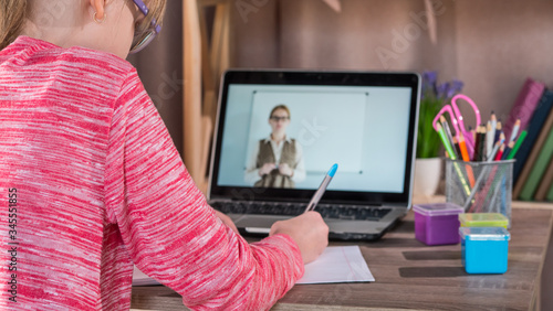 The child is engaged at home, in front of her laptop with an online lesson Fototapeta