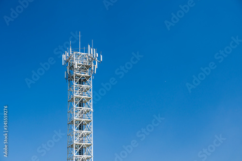 Telecommunication tower with antennas on blue sky Wallpaper Mural
