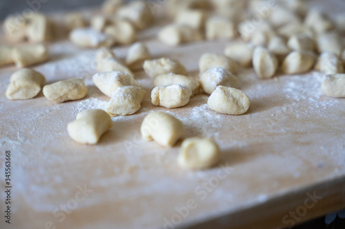 Fototapeta Homemade ricotta gnocchi floured and ready to be cooked, arranged on a wooden surface and photographed from above - Top view obraz