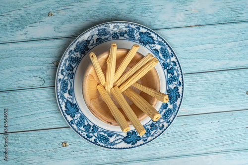 Thai Sweet Sugar Candy Look Like Stick Wood on old Ceramic Dish with Blue Wooden Canvas Print