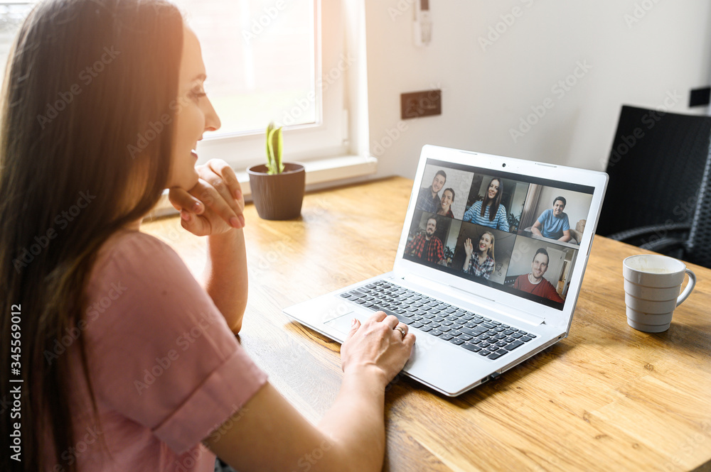 Fototapeta Communication on distance via video, video call, zoom. A young attractive woman using app on laptop for meeting with friends. She looks at webcam and smiles. Side view