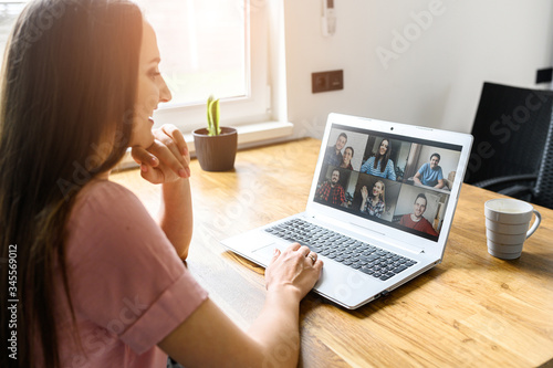 Obraz Communication on distance via video, video call, zoom. A young attractive woman using app on laptop for meeting with friends. She looks at webcam and smiles. Side view - fototapety do salonu