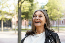 Cheerful Overjoyed Middle Aged Woman Wearing Sunglasses On Her Head And Black Leather Jacket Over White Blouse Enjoying Peaceful Beautiful Morning While Waking In Park, Looking Up With Broad Smile