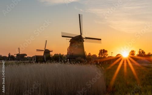 Holenderskie wiatraki nad kanałem wodnym, zachód słońca w Holandii Północnej
