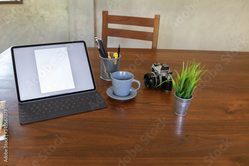 Worktable with blank  tablet, camera, coffee cup on desk. Canvas-taulu