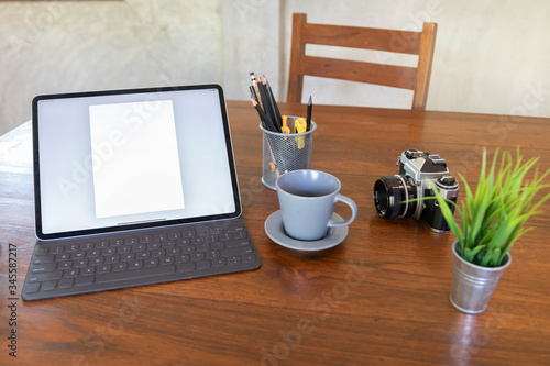 Valokuvatapetti Worktable with blank  tablet, camera, coffee cup on desk.