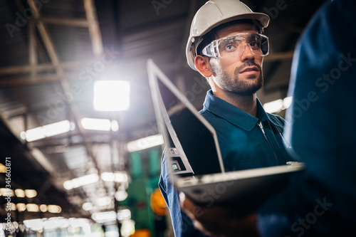 Fototapeta Industry maintenance engineer wearing uniform and safety helmet under inspection and checking production process on factory station by laptop computer Industry, Engineer, construction concept