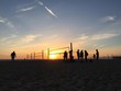 People On Beach With Volleyball Nets Against Sky At Sunset