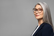 elegant asian businesswoman with grey hair in eyeglasses isolated on grey