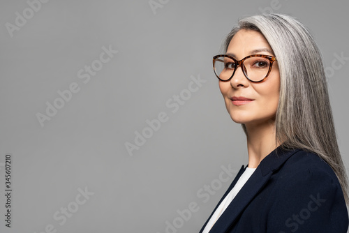 Fotografía elegant asian businesswoman with grey hair in eyeglasses isolated on grey