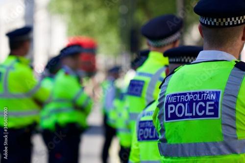 Obraz na plátně Rear View Of Police Officers Standing In City