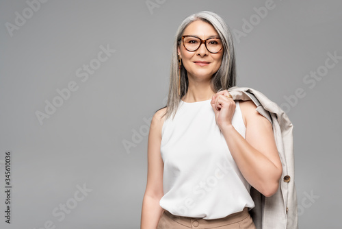 Fototapeta smiling asian businesswoman in eyeglasses isolated on grey obraz