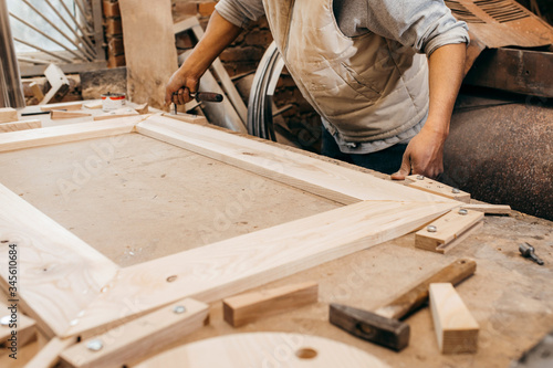 The joiner fix the woodwork in the carpentry Canvas Print