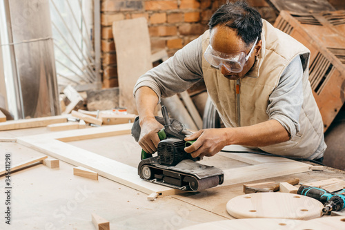 Photo Worker grinds the wood of angular grinding machine