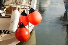 Red Buoys Hanging On Boat In Sea