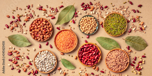 Fototapeta Legumes assortment, overhead panoramic shot on a brown background