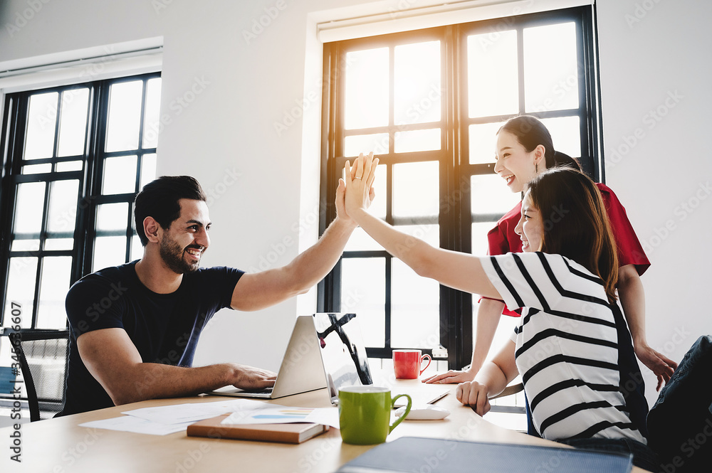 Fototapeta Successful entrepreneurs and business people achieving goals. Happy corporate team giving  high five gesture as they laugh and cheer their succeed