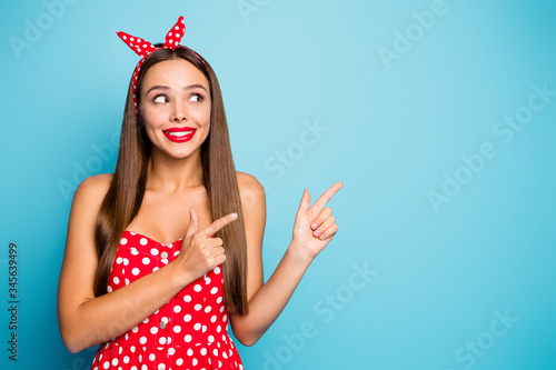 Obraz Close-up portrait of nice-looking attractive lovely glamorous curious cheerful cheery straight-haired girl showing new novelty isolated over bright vivid shine vibrant blue color background - fototapety do salonu