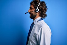 Young Handsome Call Center Agent Man With Beard Working Using Headset Over Blue Background Looking To Side, Relax Profile Pose With Natural Face With Confident Smile.