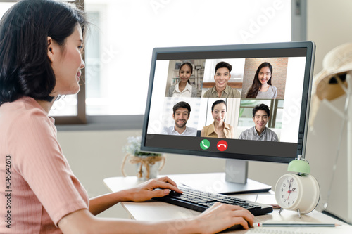 Fototapeta Asian business woman talking to colleague team about plan in video conference. Group of multiethnic business people using computer for online meeting in video call conference. Smart working from home. obraz na płótnie