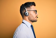 Young Business Operator Man Wearing Customer Service Headset From Call Center Looking To Side, Relax Profile Pose With Natural Face With Confident Smile.