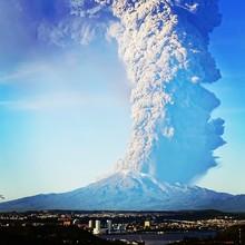 Scenic View Of Calbuco Volcano Erupting Against Blue Sky