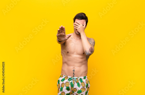young handsome man covering face with hand and putting other hand up front to st Slika na platnu