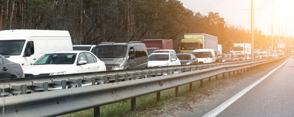 Fototapeta Highway interstate road with car traffic jam and tree forest on background. Motorway bumber barrier gridlock due country border control point. Vehicle crash accident and queue bottleneck on freeway