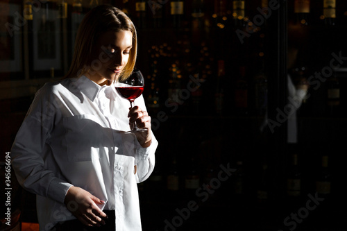 Obraz na plátně Blonde young pretty girl sommelier holding and smelling a glass of red wine
