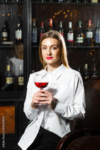 Obraz na plátne Young beautiful blonde smilling girl sommelier is holding a glass of red wine