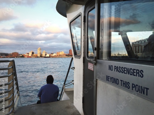 Rear View Of Man Sailing On Ferry At East River Against Sky Fototapet