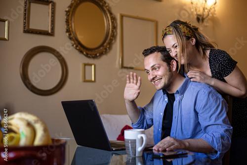 Coppia affiatata fa una video chiamata e saluta qualcuno attraverso il computer Canvas Print