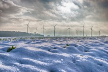 Wind Turbines In Distance On Snow Covered Landscape