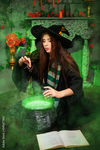 Attractive girl in the image of a witch dressed in a black hat and mantle throws an ingredient into a cauldron with an upcoming potion, sitting in a magical, green smoke Fototapete