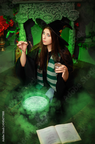 Leinwand Poster Attractive girl in the image of a witch dressed in a black hat and mantle throws an ingredient into a cauldron with an upcoming potion, sitting in a magical, green smoke