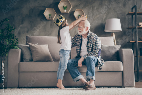 Obraz Profile photo of funny aged old grandpa golden crown head little pretty granddaughter playing famous people roles stay home quarantine safety modern interior living room indoors - fototapety do salonu