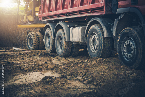 Photo Construction Site With Worker Moving Soil From Backhoe To Dump Truck