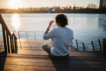 Sunset. Man Sitting On A Pier ...