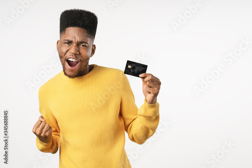 Afro american man holding credit card screaming proud and celebrating victory st Wallpaper Mural