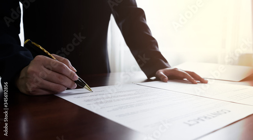 Fotomural Close up businessman or manager signing documents contract paper, lease mortgage, partnership agreement, employment with a pen making the signature , Horizontal Vintage sunlight background
