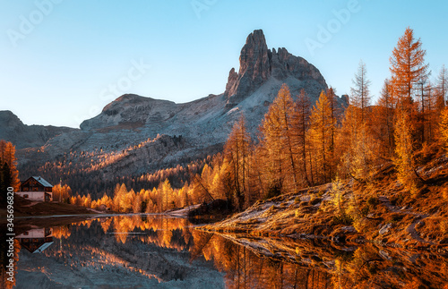 Wall mural - Fairy tale moutain lake with picturesque sky, majestic rocky mount and colorful trees glowing sunlight. Amazing nature scenery. Federa lake. Dolomites Alps.