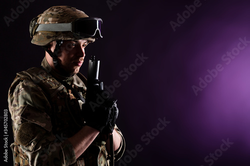 Photo Soldier with gun aims at the target on mission on violet background