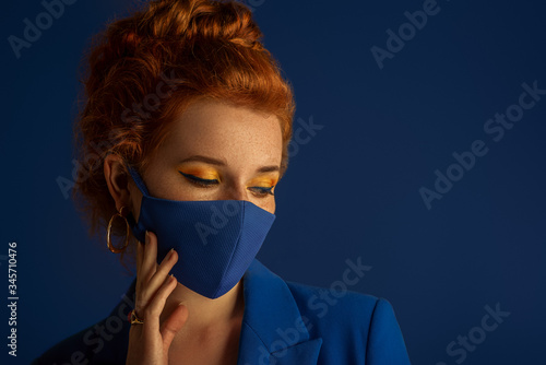 Photo Redhead woman wearing trendy fashion blue monochrome outfit with luxury designer protective face mask