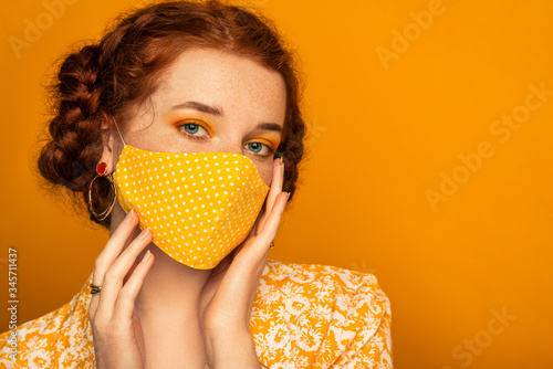 Obraz Woman wearing stylish handmade protective face mask posing on orange background.  Model with colorful eyes makeup. Fashion during quarantine of coronavirus outbreak. Copy, empty space for text - fototapety do salonu