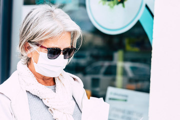 Elderly lady with mask and protective gloves outside the chemist's shop with medicines and instructions. Fear of coronavirus infection, covid-19. Concept of retired senior and fear of contagion