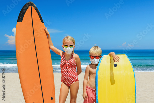 Foto Funny kids with surf boards wear protective mask on sea beach