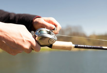 Man Holds Fishing Rod With Ree...