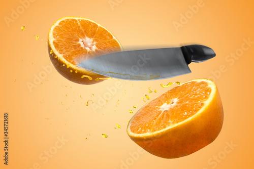 Fotomural Naranja que esta  rebanada a la mitad por un cuchillo, salpicando gotas de jugo