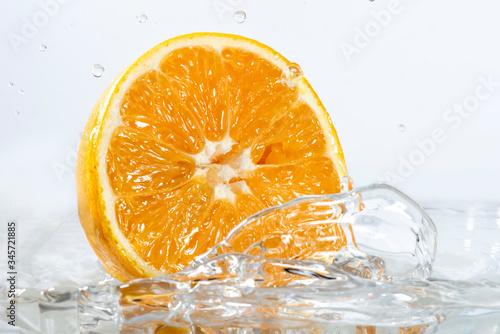 Cuadros en Lienzo Naranja rebanada por la mitad sobre una superficie liquida salpicando agua
